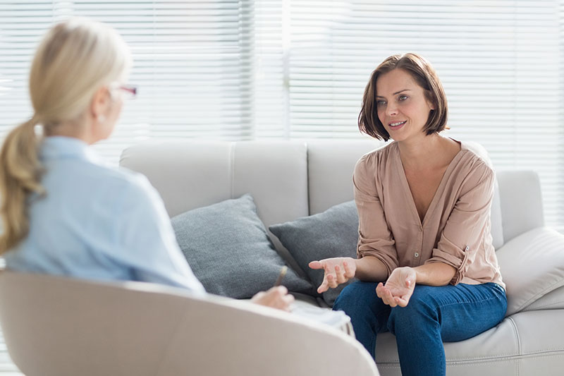 Therapist talking to client on couch