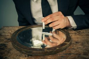 young_businessman_snorting_cocaine_off_of_mirror